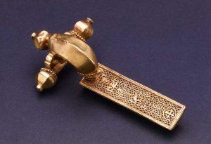 """Fibula aurea con terminazioni """"a cipolla"""", dal tesoro di Reggio Emilia rinvenuto nel 1957 e costituito da argenterie, gioielli aurei maschili e femminili e sessanta solidi (databili entro il 493 d. C.)"""